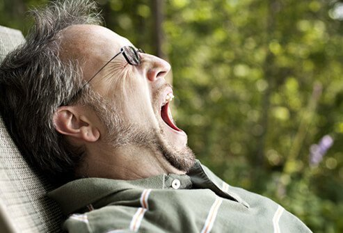 A middle-aged man yawns from fatigue.