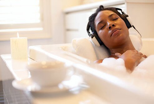 A woman relaxing in her bathtub listening to music.