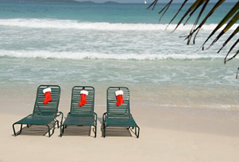 Three lounge chairs on the beach with Christmas stockings.