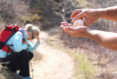 A hiker gives a fellow hiker, that's not feeling well, pain reliever medicine.