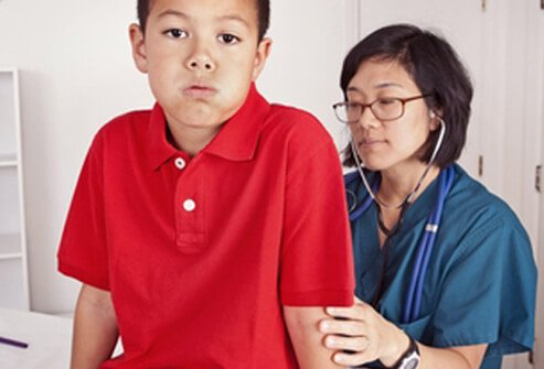 A boy feeling nauseous while being examined by a doctor.