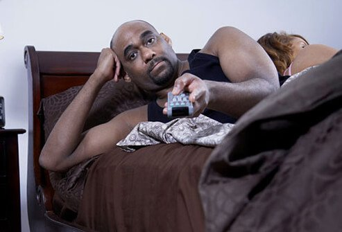 Photo of a man with the remote control in bed.
