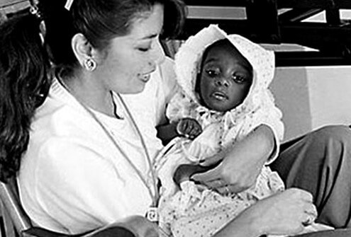 AIDS baby held by hospital worker in 1983.
