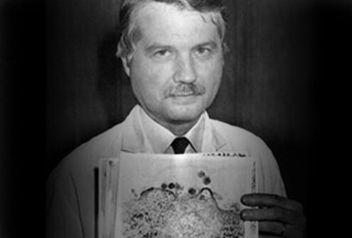 Dr. Luc Montagnier holds images of AIDS viruses.