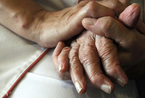 A nurse holding a patients hand.