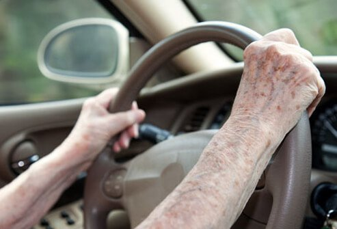 An older woman's hands on the steering wheel.