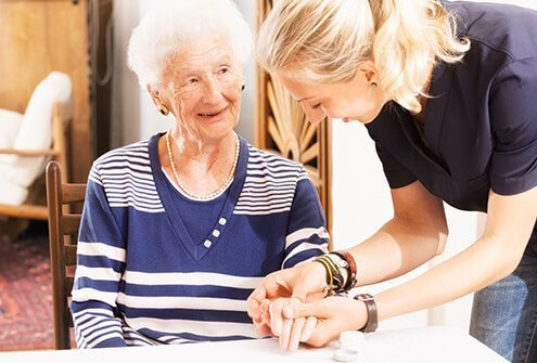 A nurse assisting a senior woman who has Alzheimer's disease.