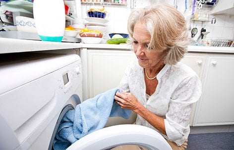 A woman with Alzheimer's disease doing the laundry.