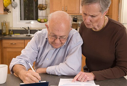 A woman helps a man with Alzheimer's disease write checks.