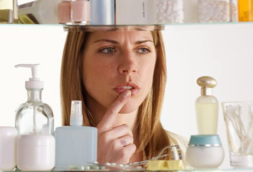 Photo of a woman choosing skin cream from a cabinet.