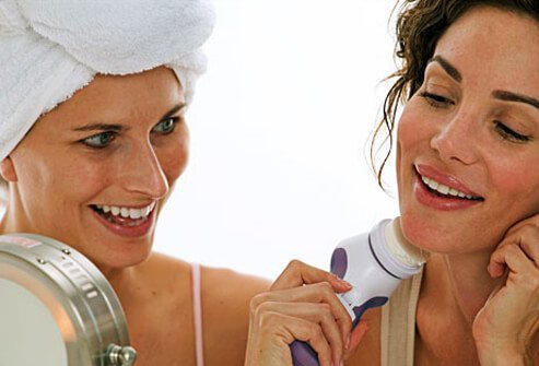Photo of two women using a spinning brush to scrub away dead skin.