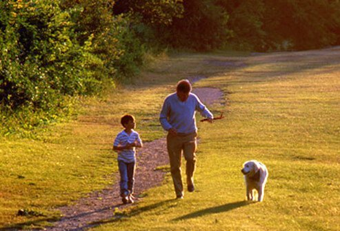 Photo of man and his grandson walking their dog.