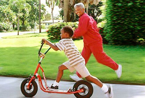 Photo of a woman racing her grandson on a bike.