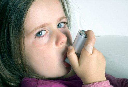 A girl with asthma uses an inhaler.