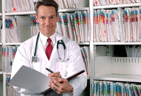 Doctor holding notebook standing next to files.