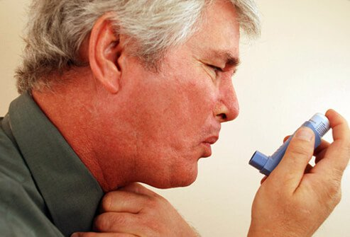 Man holding inhaler while having an asthma attack.
