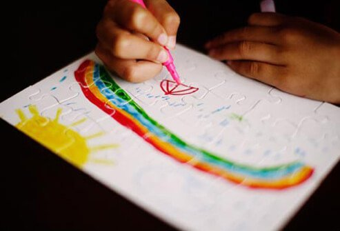 An autistic child drawing a rainbow.