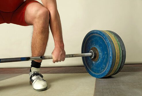 Weightlifter and heavy barbell.