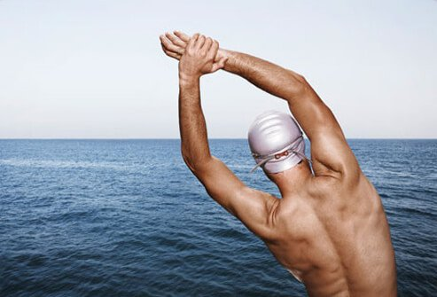A male swimmer stretches.