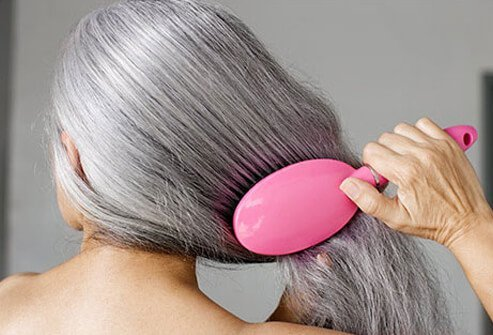 A photo of a woman brushing her gray hair.