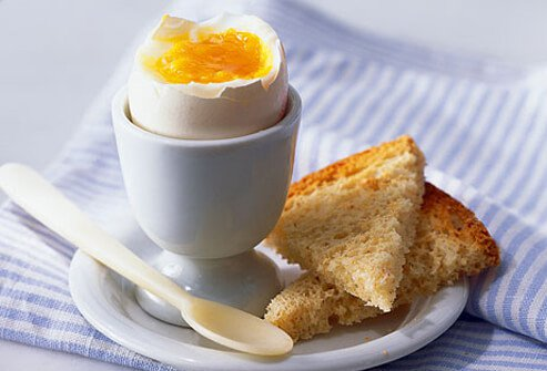 Boiled egg in a cup with wheat toast.