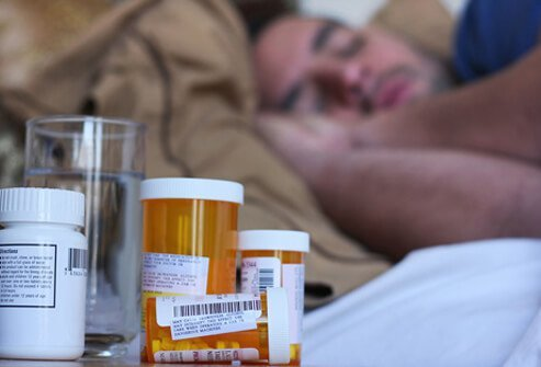 A man resting with fluids and medicine by his bed recovering from bronchitis.