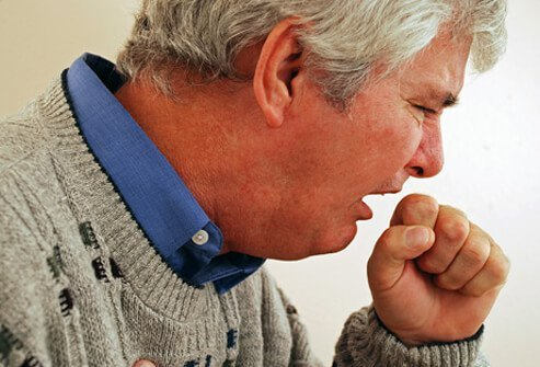 A man suffering from acute bronchitis and coughing.