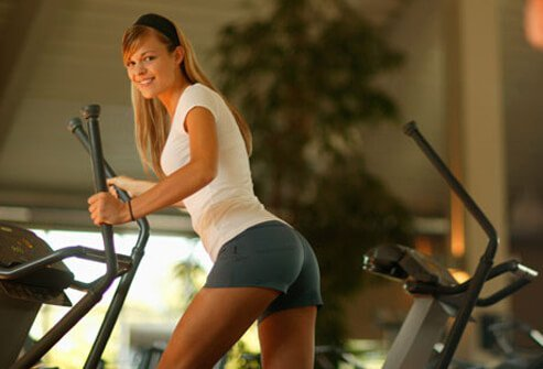 A woman in gym working out on an elliptical machine.