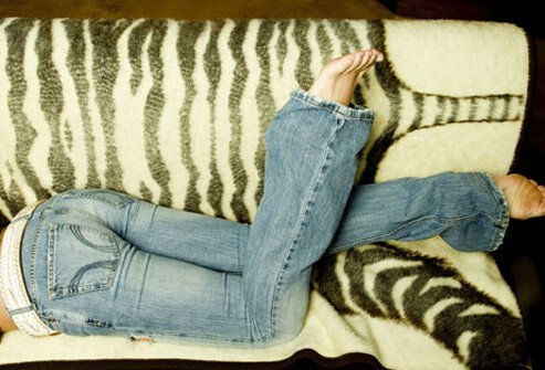 A woman laying on the couch in flared jeans.