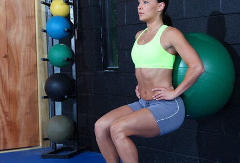 A woman doing a ball squat exercise.