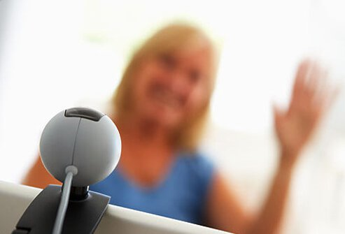Photo of woman waving to webcam.