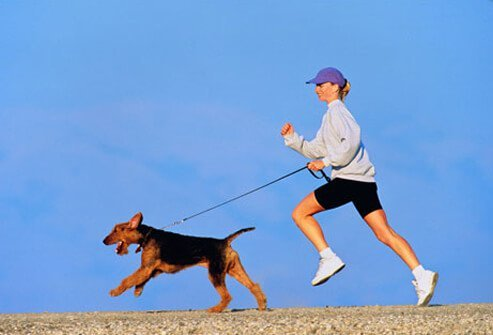 Photo of woman running with her dog.