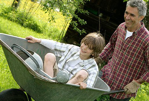 A man playing with his son in a wheelbarrow.