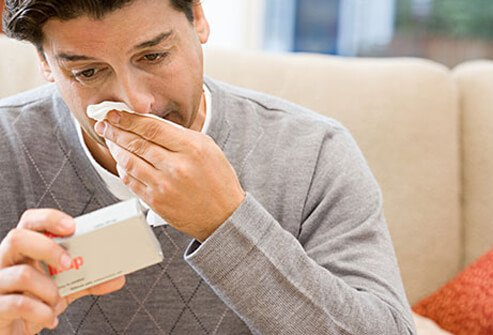 A man reading the box of anti-viral flu medication.
