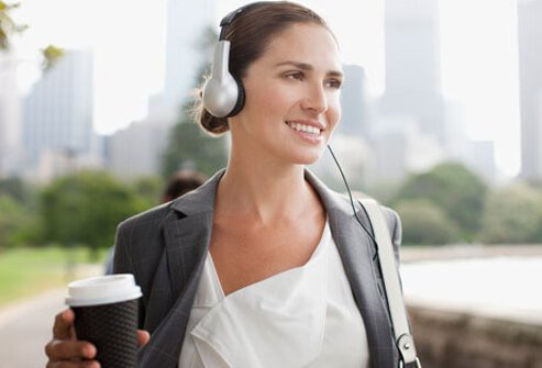 A woman walking with headphones.