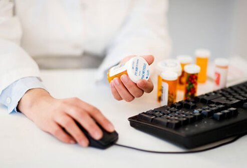 Pharmacist holding pills at a computer.