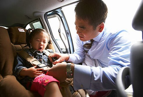 Photo of father buckling his daughter into her car seat.