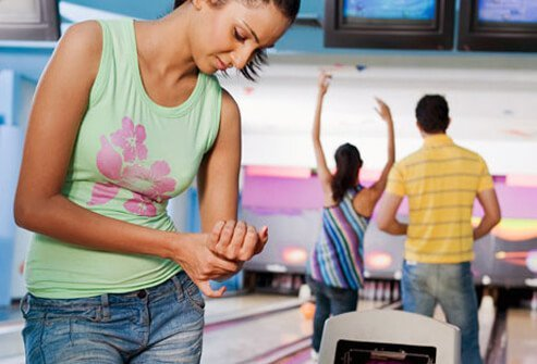 A young woman suffers a sprain or strain in her wrist from bowling.