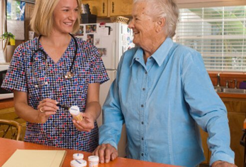 A caregiver helping an elderly dementia patient with her medications.