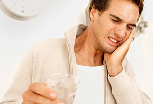 A man experiences tooth sensitivity while drinking ice water.
