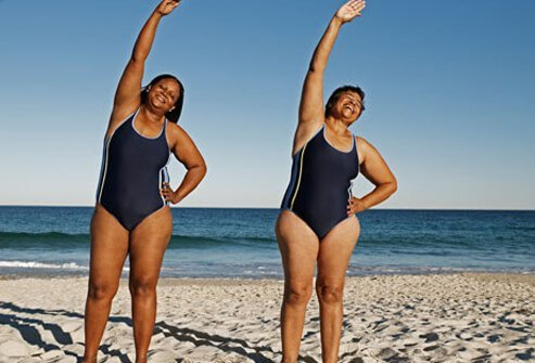 Two women exercising slowly at a beach.