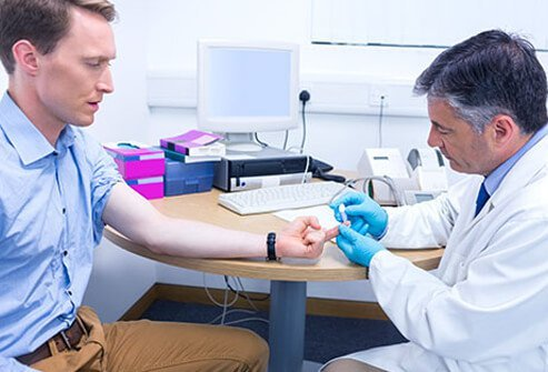 A doctor checking a male patient's blood sugar levels.