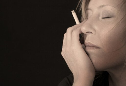 Woman smoking with eyes closed.