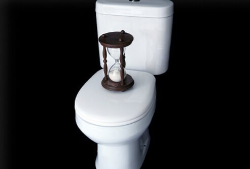 Toilet with an hourglass timer on it.