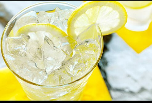 Lemonade in a glass with a lemon garnish.