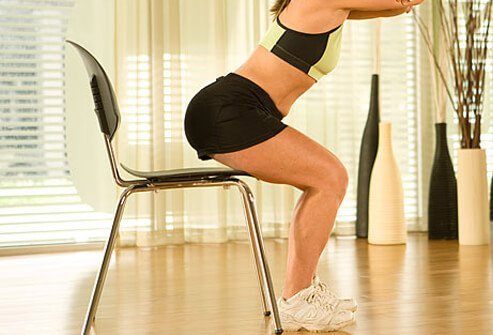 Trainer using a chair to perform squat