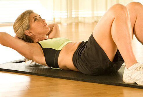 Trainer demonstrating proper form for crunches