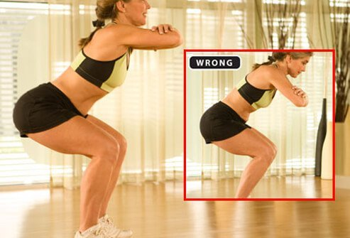 A trainer demonstrating the proper form for squats.