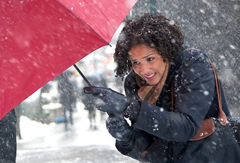 A woman shields herself with an umbrella from blizzarding snow.