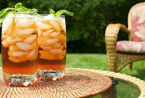 Two glasses of iced tea garnished with mint leaves.